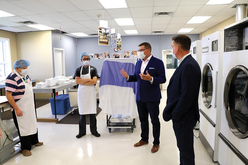 Saskatchewan Premier Scott Moe and Moosomin MLA Steven Bonk visit with Moosomin Kin-Ability Centre clients Ryan Bender and Barry Gessell while learning about the hospital laundry services offered at the Kin-Ability Centre.