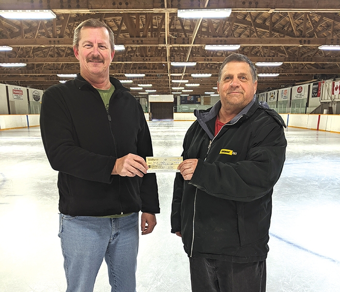 Allan Holloway, right, presented a cheque in the amount of $8,036.54 to the town of Wapella on Tuesday. The cheque was the proceeds from the Dakota Holloway Memorial Hockey Tournament held on Jan. 24 and will be used for the Wapella Rink. Deputy Mayor Brian Schinke, left, accepted the cheque.