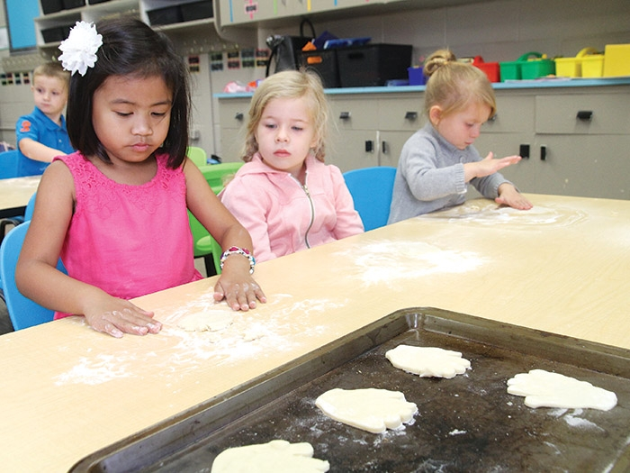 "<b>First week of school</b> Classes started in the Southeast Cornerstone School Division last Tuesday. At left are MacLeod Elementary School Kindergarten students Jaeden, Evann and Kaydence making ""kissing hand"" cookies on their third day of class after reading a story called ""The Kissing Hand"" in Mrs. McMullen's class."