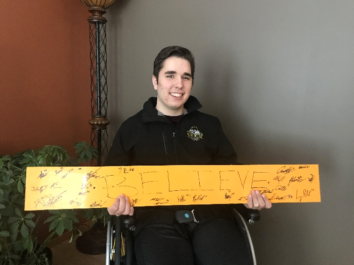"Morgan Gobeil with the ""Believe"" sign Humboldt Broncos Assistant Coach Chris Beaudry brought to the hospital in Saskatoon just days after the accident. The sign stayed at the hospital until the last boy—Morgan— came home, just as Beaudry intended."