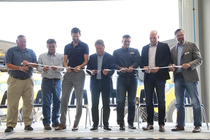 Cutting the ribbon to officially open the new Mazergroup location in Moosomin. From left are Moosomin Mayor Larry Tomlinson, Randy Tye, VP of Inventory Management, Chris Finley, VP of Parts and Service, Bob Mazer, the President and CEO of Mazergroup cutting the ribbon, Andrew Marshall, Canadian Sales Manager for New Holland, Brad Tarr, the VP of Sales and Marketing, and Wally Butler, the VP of Finance and Administration.
