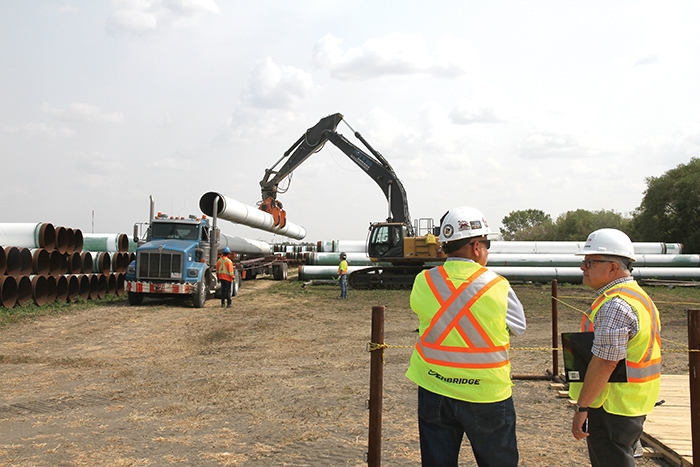 Al Sawatzky, Construction Manager, Line 3 Replacement Program with Enbridge Pipelines, left, and federal Minister of Public Safety Ralph Goodale watch as pipe is loaded up for the Enbridge Line 3 replacement. The town and RM of Moosomin are trying to revive consideration of another pipeline project--Energy East.