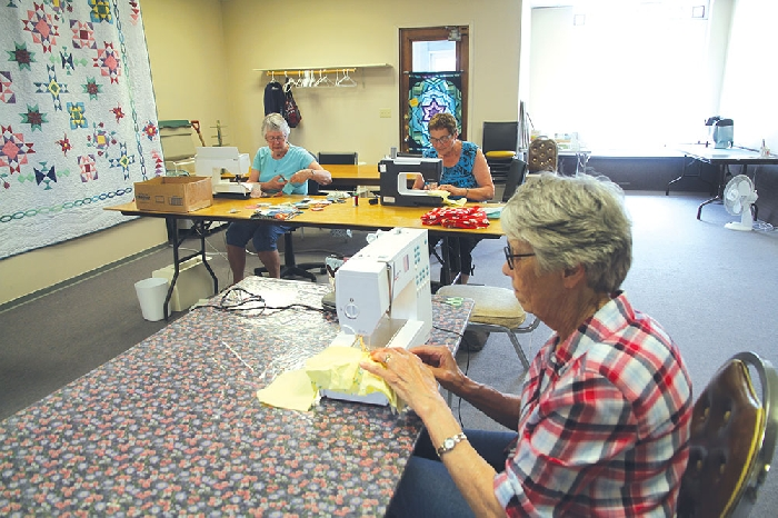 Some of the comfort quilters working on bags and receiving blankets for True North Aid.