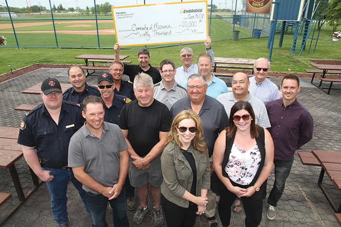 Enbridge contributed $60,000 to projects in Moosomin in a cheque presentation at the Tim Hortons Outdoor Eventplex on Wednesday, June 13 -- $35,000 will go toward developing an outdoor event-plex and a hot tub project, while $25,000 will be used by the Moosomin Fire Department toward purchase of a new aerial platform truck. Pictured are (front row, from left) Ryan Kitchen and Joanne Bradbury, Enbridge; Catherine Mannle (assistant recreation director). Second and third rows (from left):  Peter Nabholz, Chief Rob Hanson, Mike Cooper and Trevor Green (Moosomin Fire Department); Murray Gray (counc