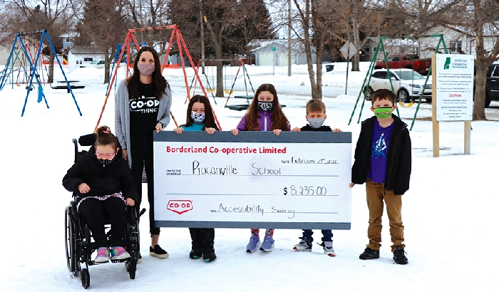 Borderland Co-op Community Relations Manager Savannah Roden presents Rocanville School students (left to right) Sofia Laidlaw, Lilly Jackson, Ella Bock, Corbin Minty, and Odin Rosti with a cheque for $8,235 to go towards the school's wheelchair swing project.