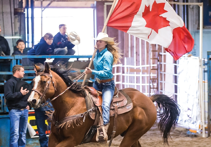 Joelle Garvey carries the Canadian flag during the opening of the Dodge City Days Rodeo in Wapella last year. Kim Poole took this great photo.