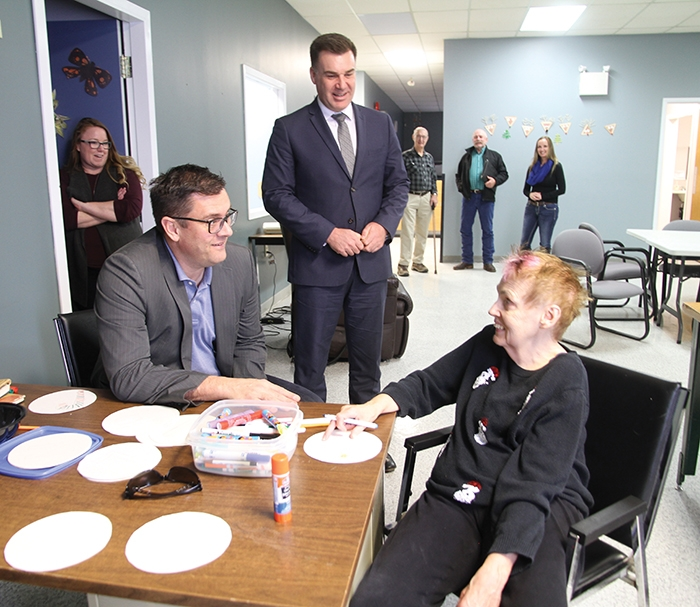 Moosomin MLA Steven Bonk, standing, and Saskatchewan Social Services Minister Paul Merriman, seated, visited the Pipestone KinAbility Centre in Moosomin Thursday. Minister Merriman chats with Brenda Sopp as the two share a few laughs.