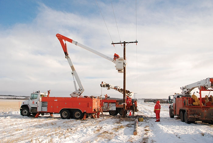 SaskPower crews inspecting and repairing power poles.