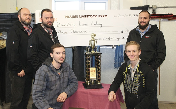 Above are some of the Boundary Lane Colony hog barn crew with their trophy and cheque. In back from left are Ken, Clinton, and Bryan Kleinsasser. In front are Mateo and Jesse Kleinsasser.
