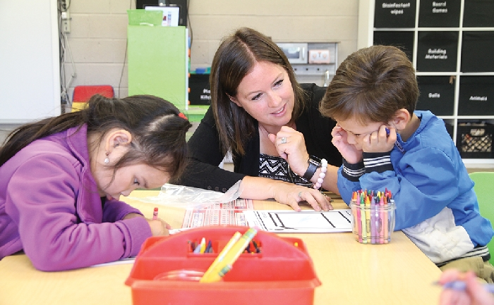 Students were back to school last week as classes resumed for the 2019-20 school year. Above, Mrs. McMullen at MacLeod Elementary School in Moosomin teaches Kindergarten students Marjela and Liam how to draw a picture of themselves and write their names on their first day of school.